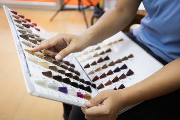 Vrouw met haarkleurstalen en wijzende vinger selecteren op kleur van haarkleurmiddelen. haarkleuring in een kapsalon.