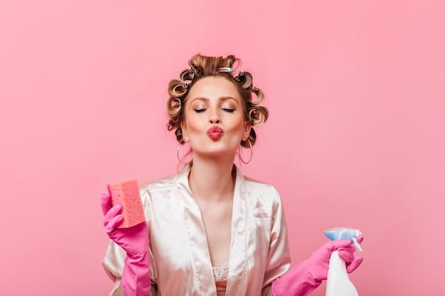 Vrouw met haarkrulspelden op haar hoofd houdt spons voor de afwas en blaast kus op roze muur