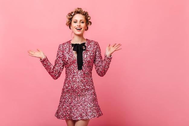 Vrouw met haarkrulspelden vormt op roze muur in glinsterende jurk
