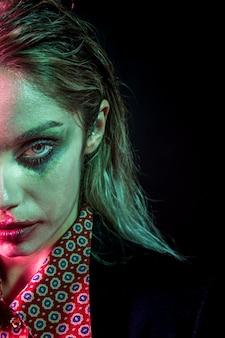 Vrouw met halloween-make-up van het joker de halve gezicht