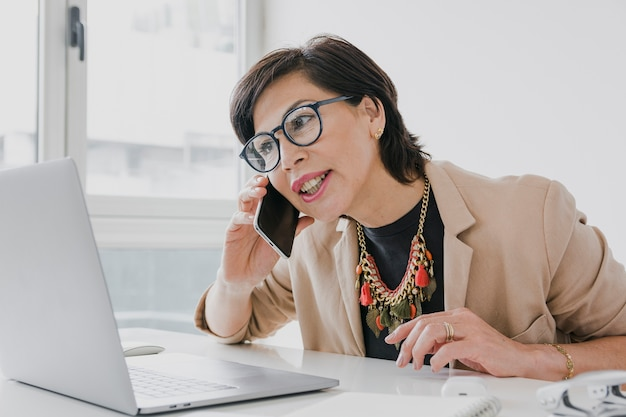 Vrouw met halsband die op de telefoon op haar bureau spreekt