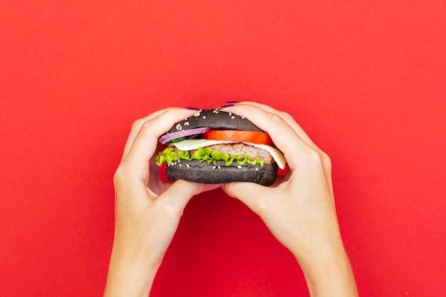 Vrouw met hamburger over rode tafel