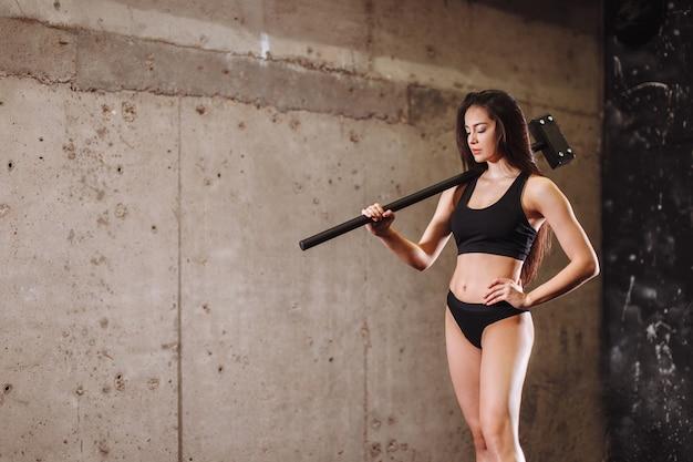 Vrouw met hamer in de sportschool. meisje met voorhamer in opleiding