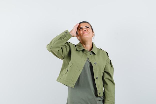Vrouw met hand boven het hoofd terwijl het opzoeken in jas, t-shirt en op zoek vrolijk