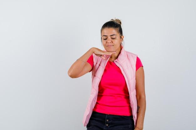 Vrouw met hand onder kin in t-shirt, vest en ziet er leuk uit