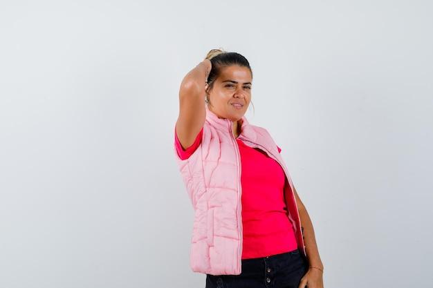 Vrouw met hand op hoofd in t-shirt, vest en er ontspannen uit
