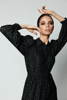 Vrouw met hand op hoofd lichte make-up zwarte jurk studio
