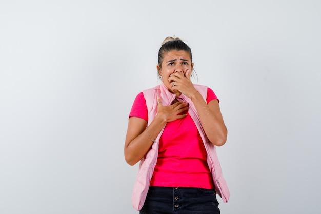 Vrouw met hand op mond in t-shirt, vest en weemoedig kijkend