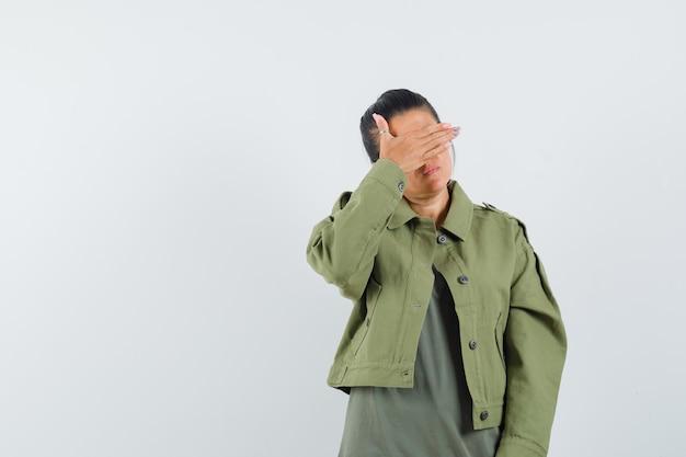 Vrouw met hand op ogen in jasje, t-shirt en kalm op zoek.