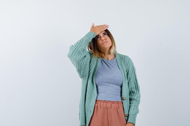 Vrouw met hand op voorhoofd in vrijetijdskleding en vergeetachtig op zoek. vooraanzicht.