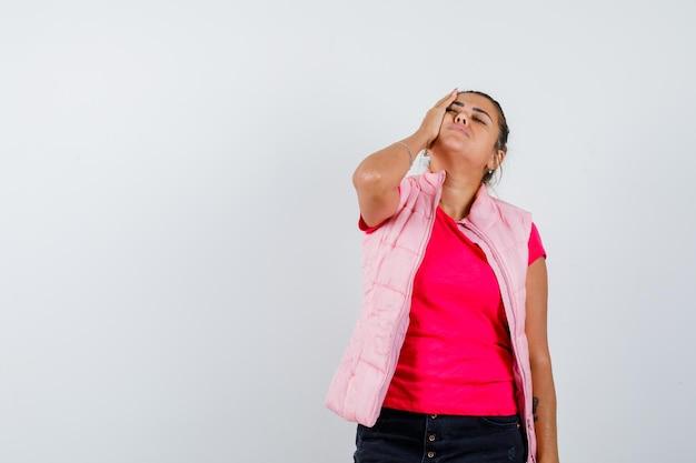 Vrouw met hand op wang in t-shirt, vest en hulpeloos kijkend