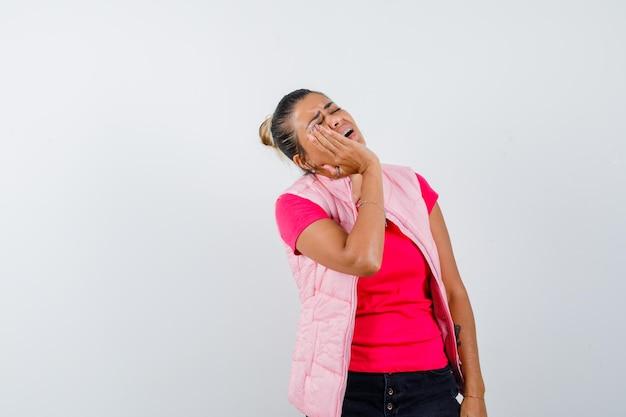 Vrouw met hand op wang in t-shirt, vest en treurig kijkend