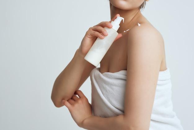 Vrouw met handdoek blote schouders lotion schone huidverzorging