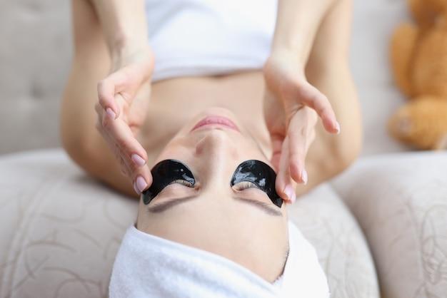 Vrouw met handdoek op haar hoofd die zwarte vlekken onder ogen plakt.
