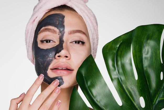 Vrouw met handdoek op haar hoofd na het douchen brengt reinigingsmasker op gezicht aan