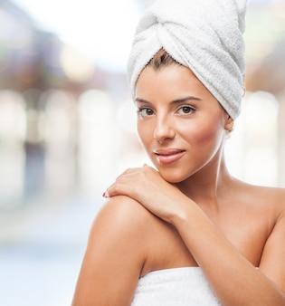 Vrouw met handdoek op het hoofd te raken schouder