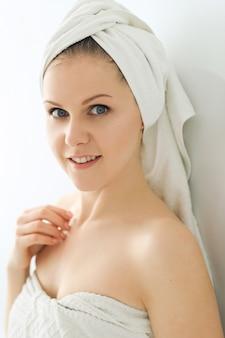 Vrouw met handdoek op hoofd en lichaam na het douchen