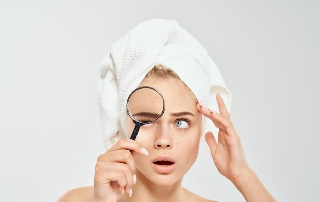Vrouw met handdoek op hoofd vergrootglas in hand naakte schouders cosmetologie dermatologie