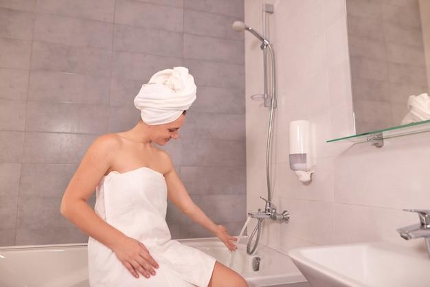 Vrouw met handdoek op hoofd vult bad met water en probeert de watertemperatuur met haar hand