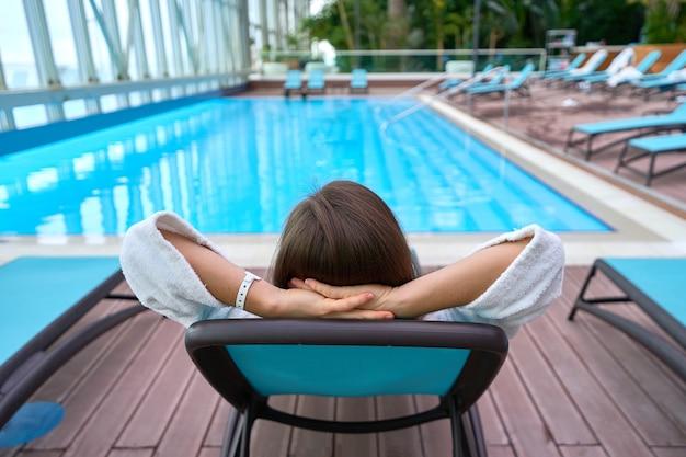 Vrouw met handen achter het hoofd liggend op een ligstoel bij het zwembad terwijl u ontspant in een wellness-kuuroord. gemakkelijke levensstijl en tevredenheid