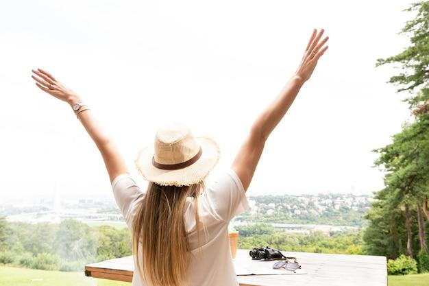 Vrouw met handen in de lucht van achteren