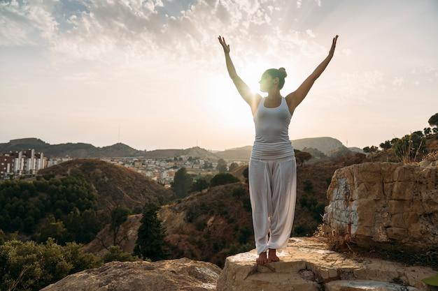 Vrouw met handen omhoog tijdens yoga sessie