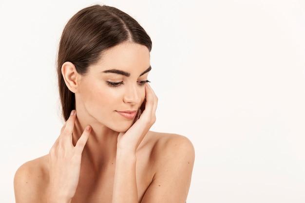 Vrouw met handen op haar nek en neerkijken