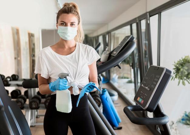 Vrouw met handschoenen die gymnastiekapparatuur met medisch masker schoonmaken tijdens de pandemie