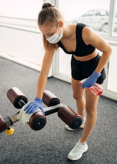Vrouw met handschoenen en medisch masker op de desinfecterende uitrusting van de sportschool