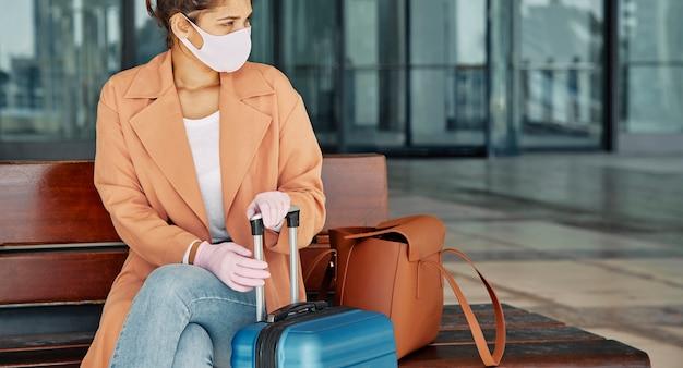 Vrouw met handschoenen en medisch masker op de luchthaven tijdens pandemie