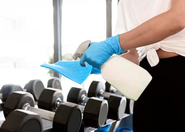 Vrouw met handschoenen en reinigingsoplossing fitnessapparatuur desinfecteren