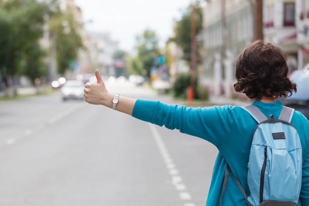 Vrouw met handtas die een taxicabine begroeten die in stadsstraat lopen