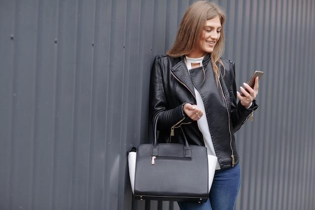 Vrouw met handtas te kijken naar haar mobiele telefoon