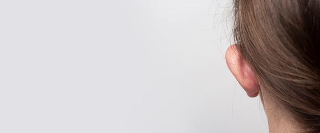 Vrouw met hangende oren uitpuilend oor achteraanzicht op een lichte achtergrond. otoplastiek, kunststof van de oorschelp. banier.