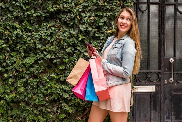 Vrouw met heldere boodschappentassen en smartphone buiten