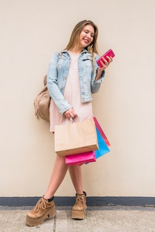 Vrouw met heldere boodschappentassen met behulp van de telefoon