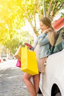 Vrouw met heldere boodschappentassen met behulp van smartphone op auto