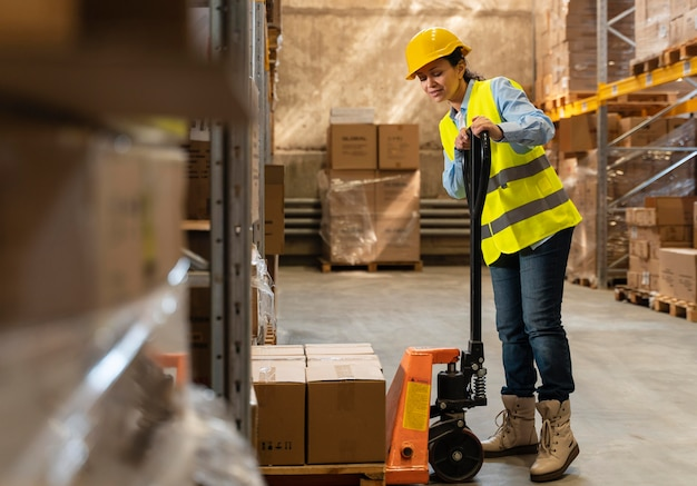 Vrouw met helm die in magazijn werkt
