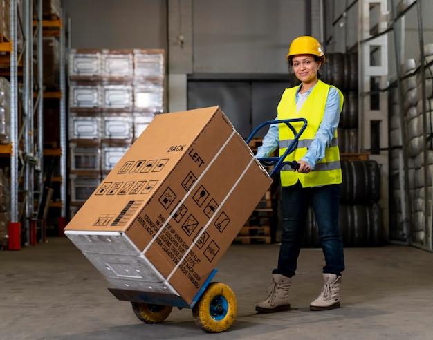 Vrouw met helm dragende dozen
