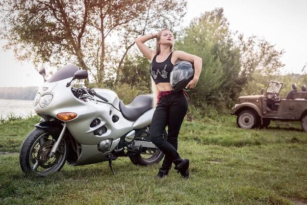 Vrouw met helm in haar hand, staat dichtbij motorfiets