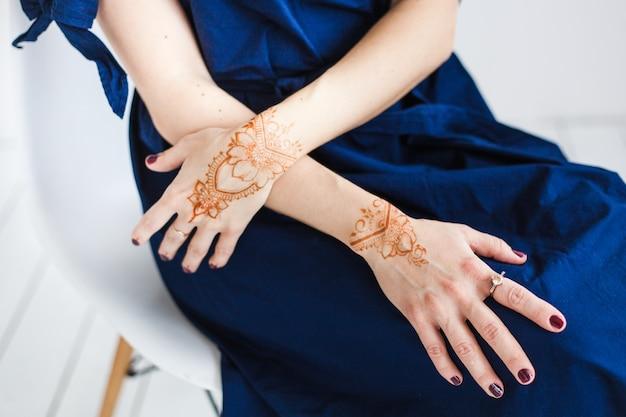 Vrouw met henna puttend uit handen, mahendi