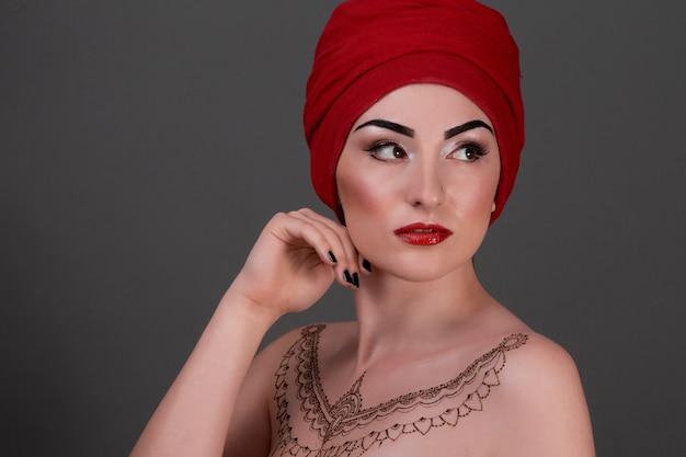 Vrouw met henna tatoeage en rode tulband