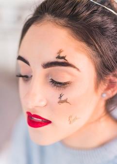 Vrouw met herten spangles op gezicht