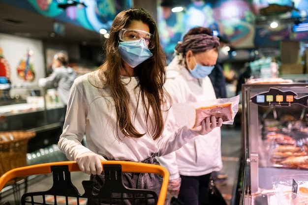 Vrouw met het chirurgische masker en de handschoenen is winkelen in de supermarkt