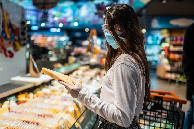 Vrouw met het chirurgische masker en de handschoenen winkelt in de supermarkt na een coronavirus-pandemie. het meisje met chirurgisch masker gaat kaas kopen.