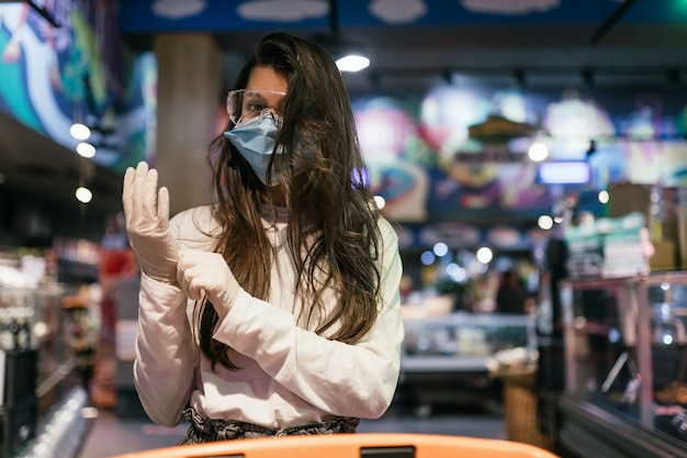 Vrouw met het chirurgische masker en de handschoenen winkelt in de supermarkt