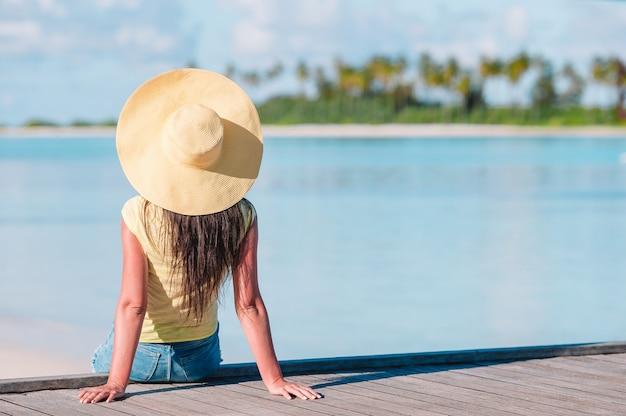 Vrouw met het gele hoed ontspannen bij zwembad in exotische toevlucht