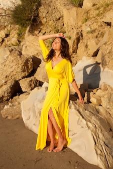 Vrouw met het lange gele kleding openlucht stellen