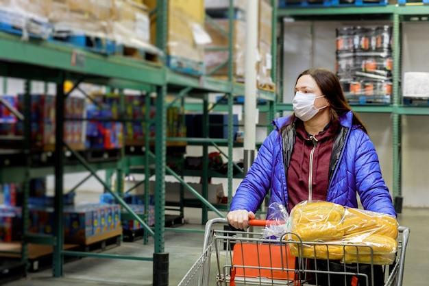 Vrouw met het masker van het beschermingsgezicht en boodschappenwagentje bij supermarkt.