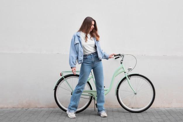 Vrouw met het stuur van de fiets buitenshuis